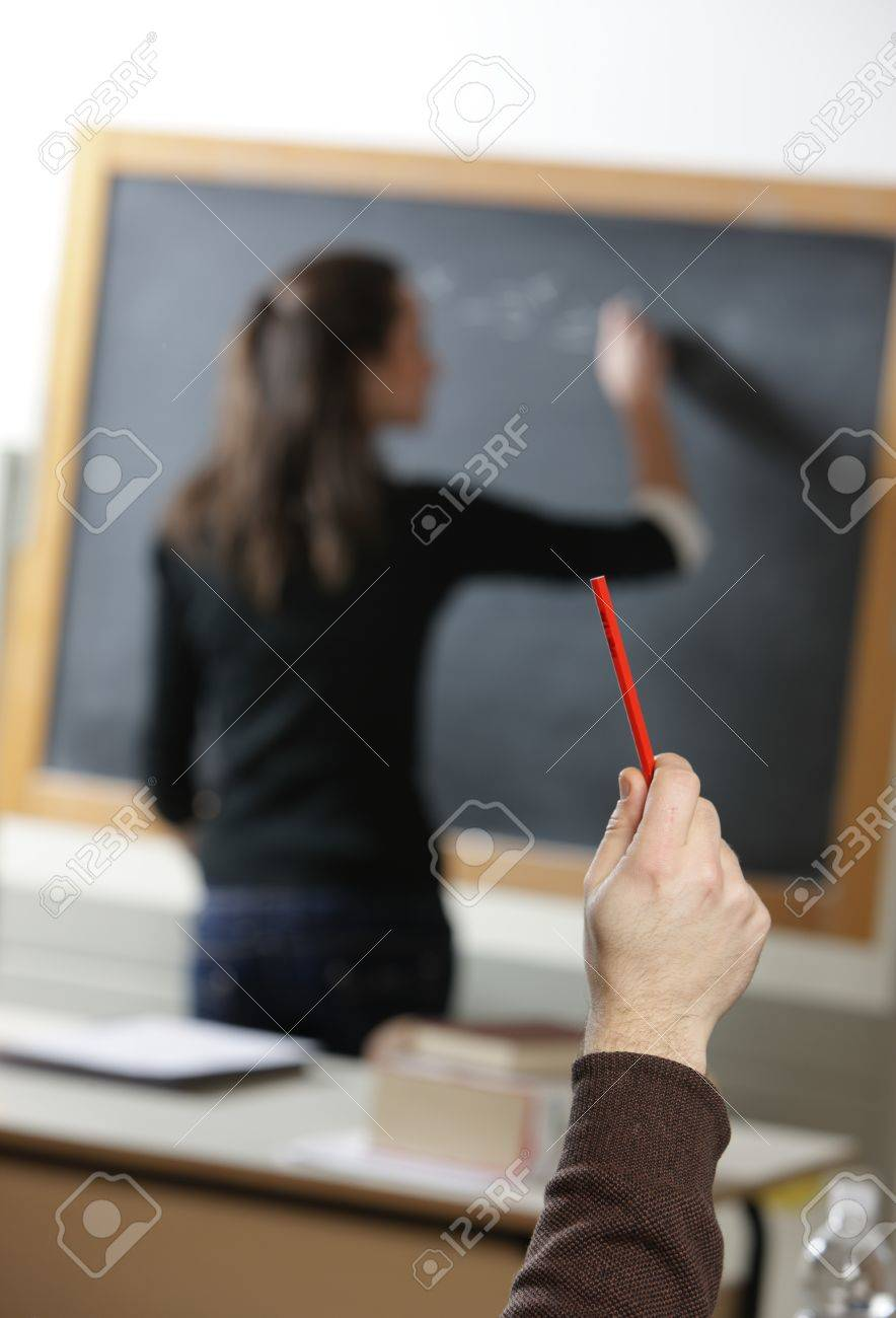 a student asks a question to the teacher that writes on the blackboard Stock Photo - 12577551