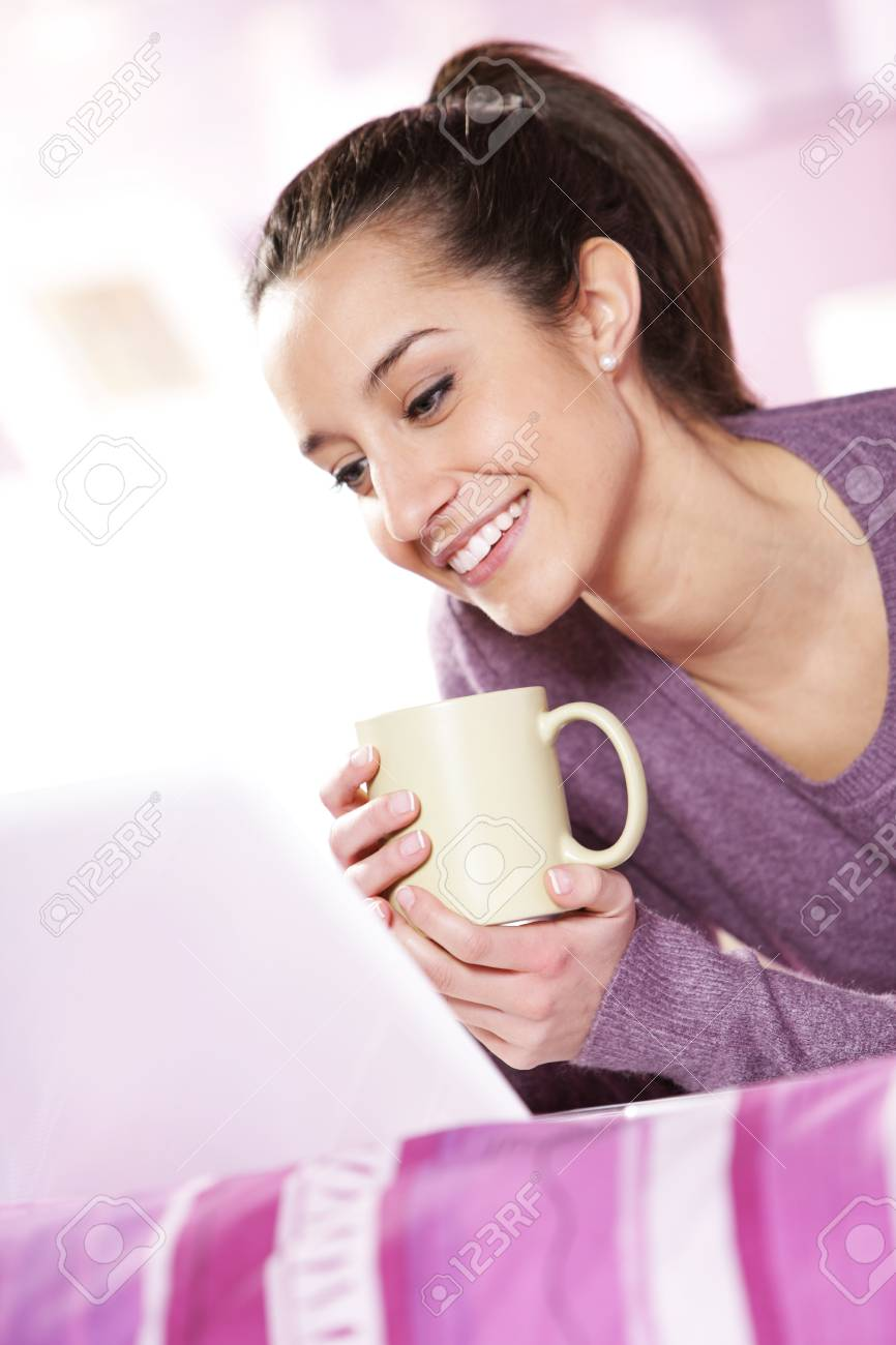 pretty girl smiles at the laptop with a cup of coffee in hand Stock Photo - 12842849