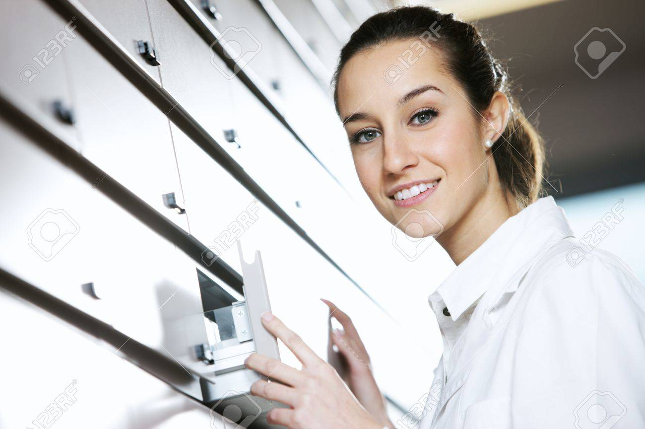 Young female pharmacist reaching for medicine Stock Photo - 12845035