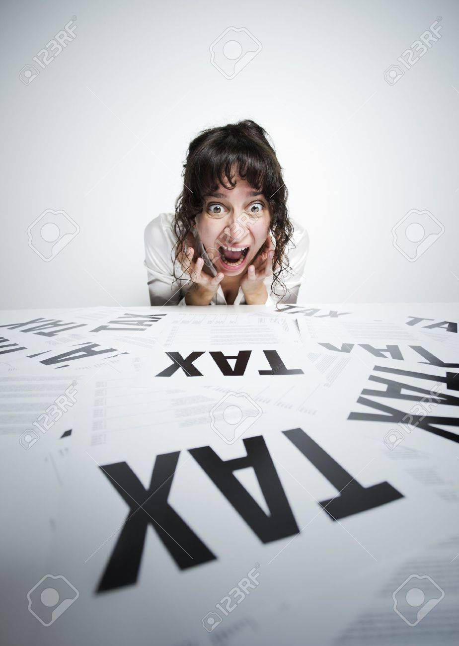 Astonished woman looking at a bunch of worrying tax forms on her desk Stock Photo - 15037942