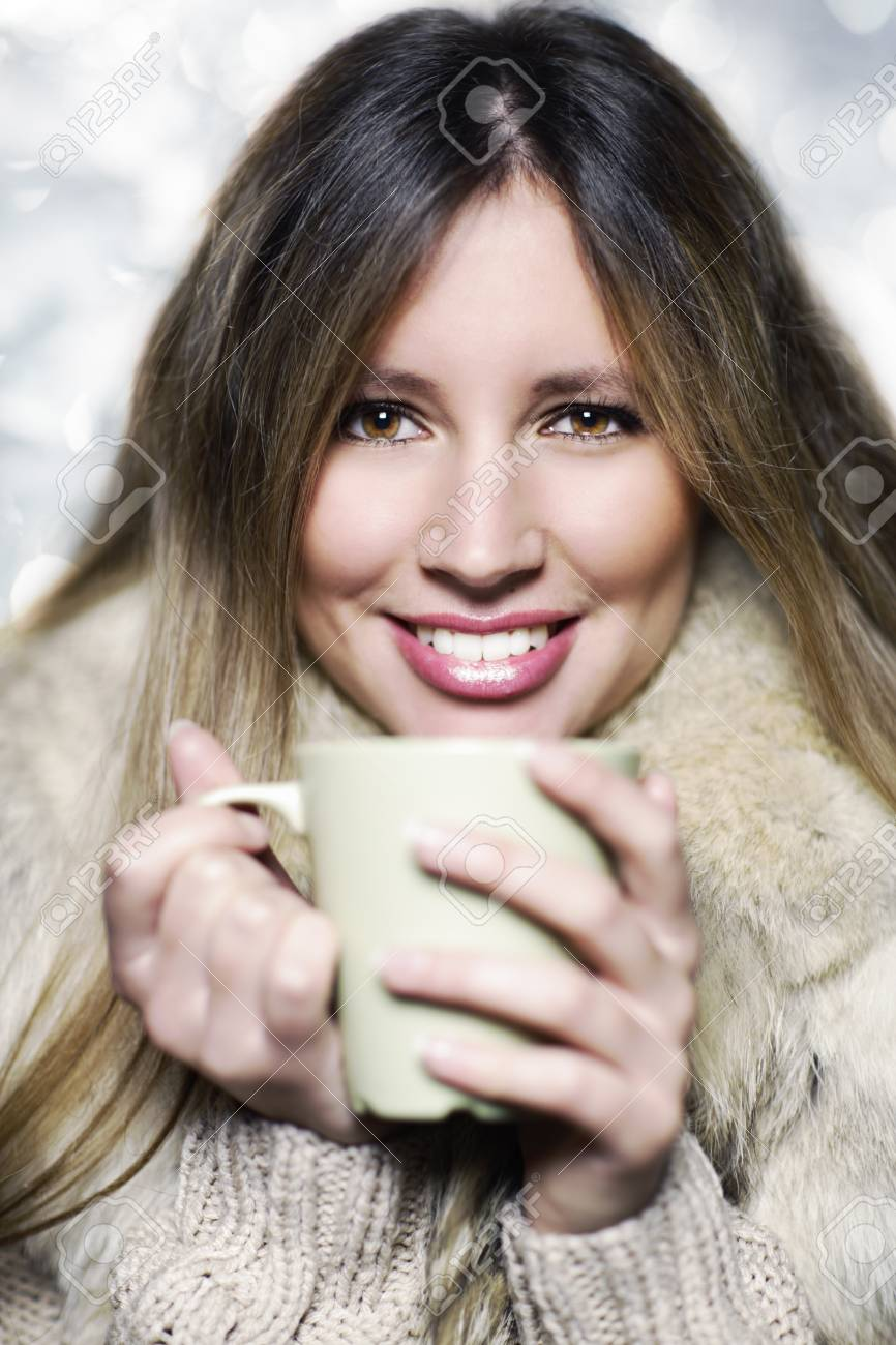 Young woman wearing winter clothes having a hot drink Stock Photo - 17408798