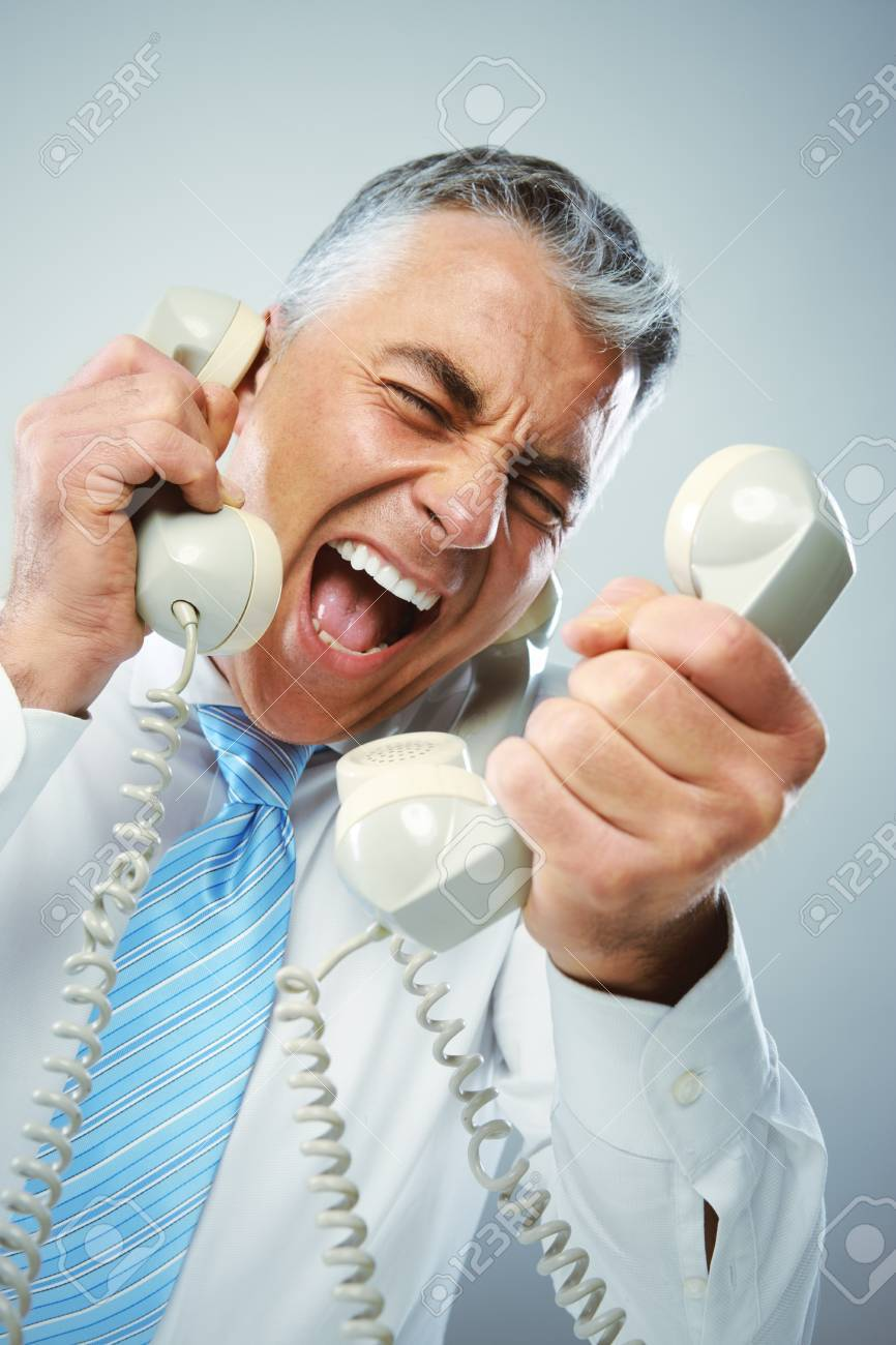 A stressed businessman yells loudly into the three handsets that he is holding. Stock Photo - 20143151