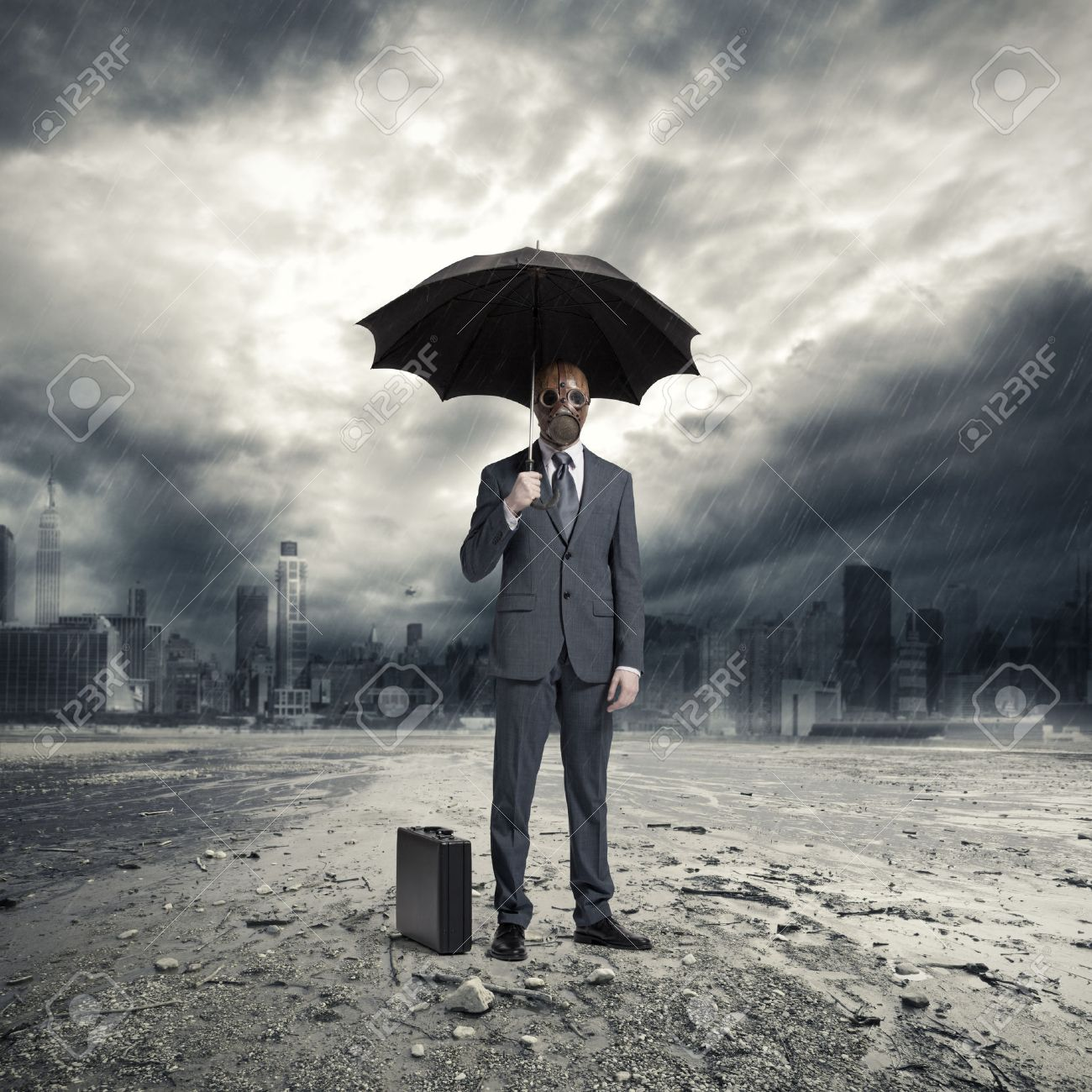 a businessman wearing a gas mask standing in the rain stock photo