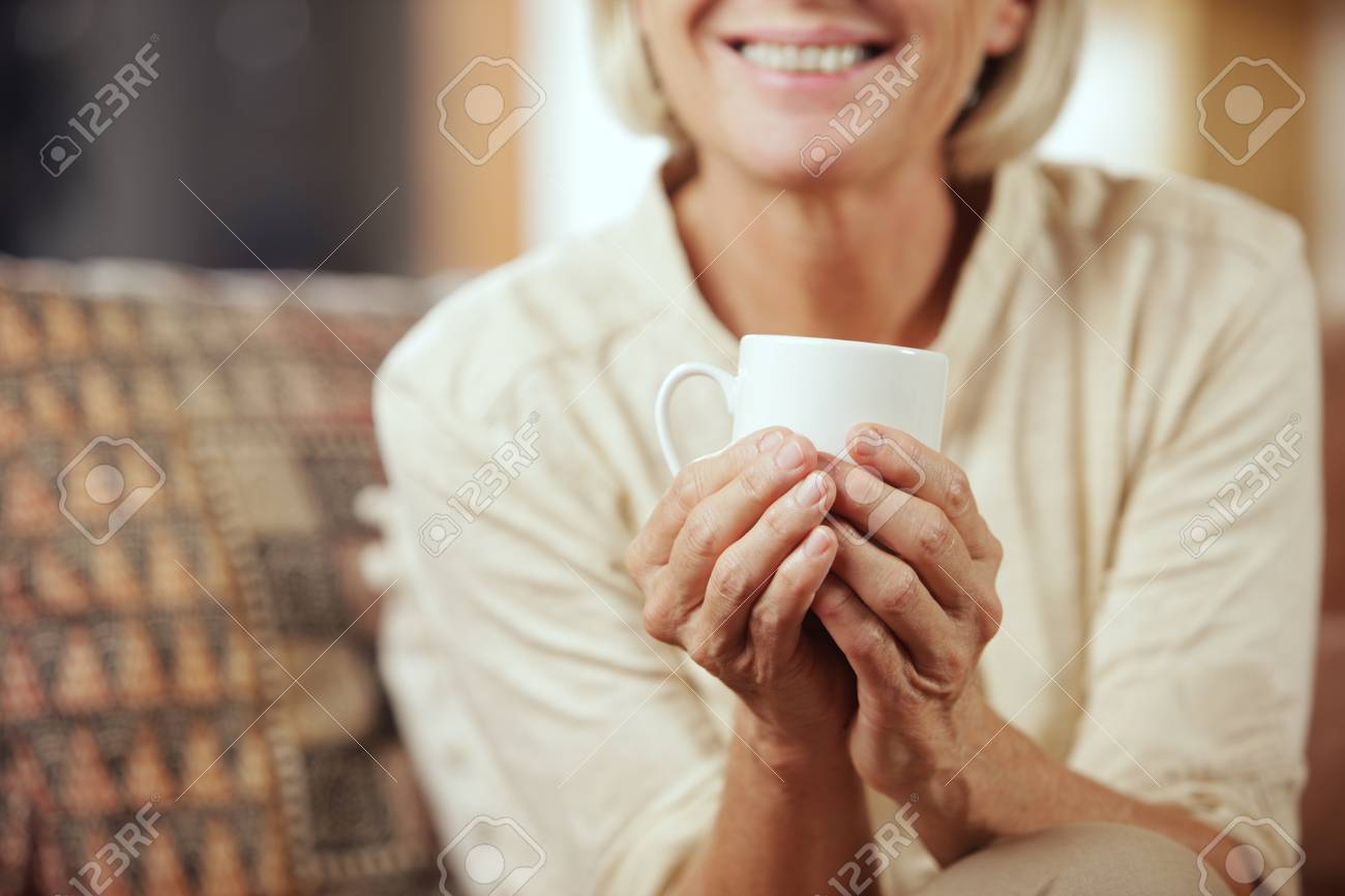 A pretty senior woman enjoying a cup of coffee, close up Stock Photo - 23159924