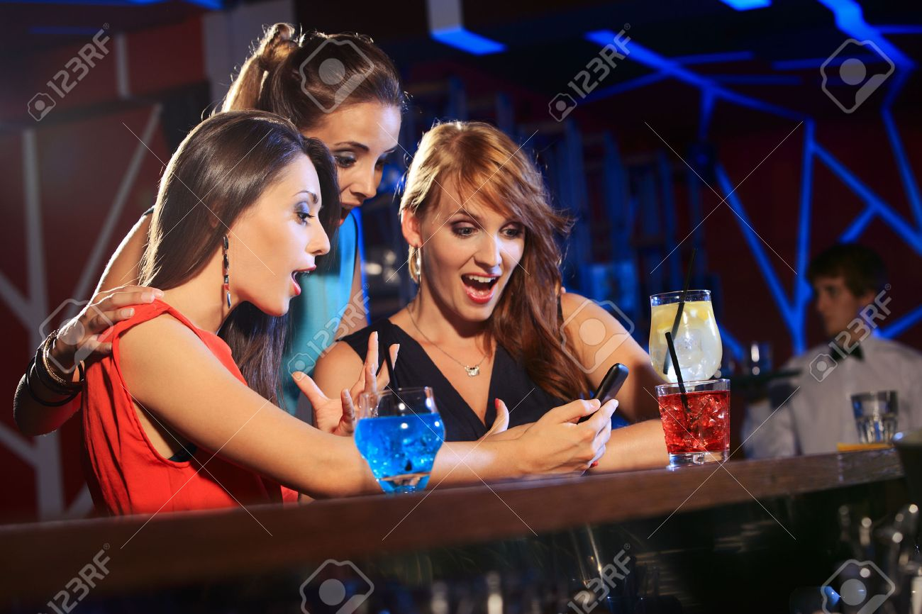 Three beautiful young women friends having fun looking at something funny on their smartphone and laughing Stock Photo - 23389729