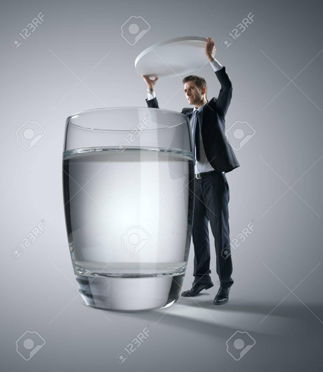 Homme d'affaires mettant une énorme pilule dans un verre d'eau.