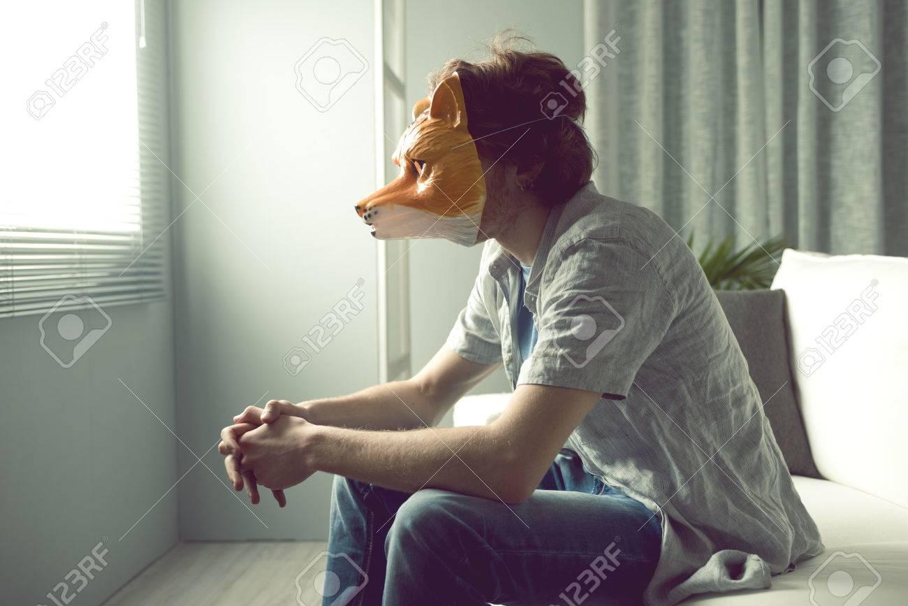 giovane uomo che indossa una maschera di volpe seduta sul divano ... - Divano Davanti Finestra
