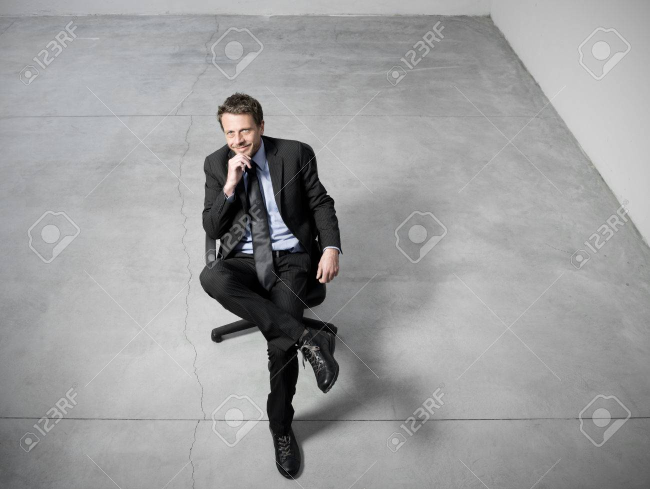 Smiling businessman sitting on an office chair with hand on chin against concrete floor background. Stock Photo - 27916030