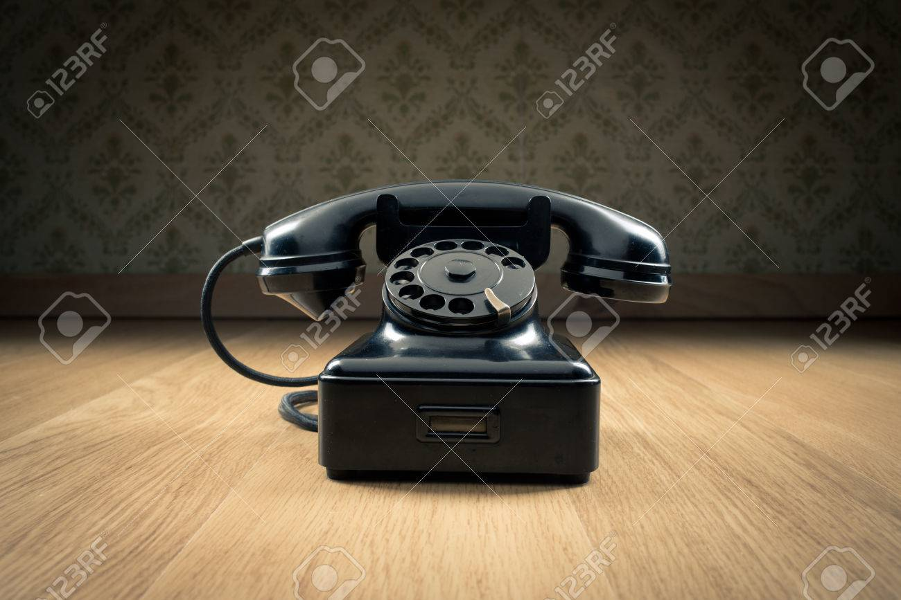Black 1950s Style Phone On Hardwood Floor And Vintage Wallpaper
