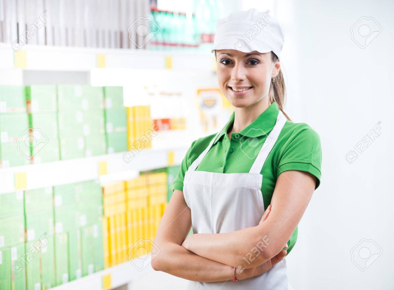 young female s clerk crossed arms smiling at camera stock photo young female s clerk crossed arms smiling at camera supermarket shelf on background