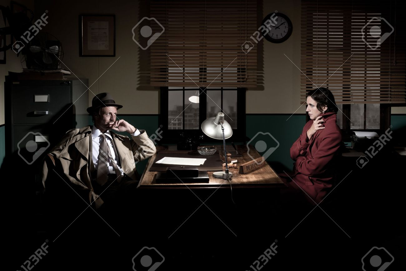 Handsome detective at office desk interviewing a young woman