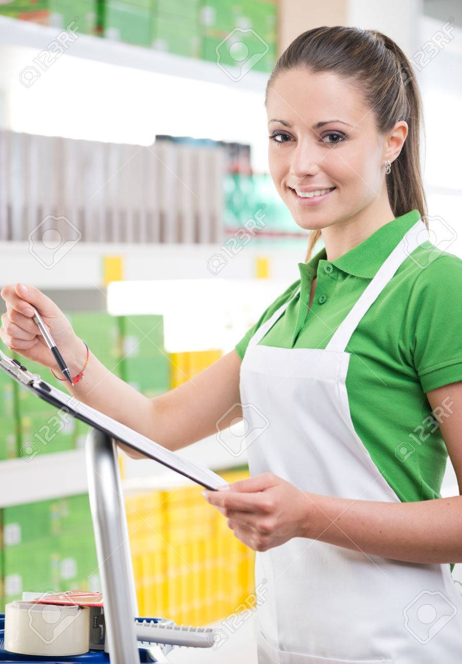 attractive female s clerk at work holding a clipboard attractive female s clerk at work holding a clipboard supermarket shelf on background stock