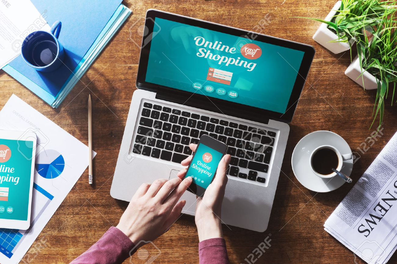Internet Home Shopping Online Shopping Website On Laptop Screen With Female Hands Using A Smartphone