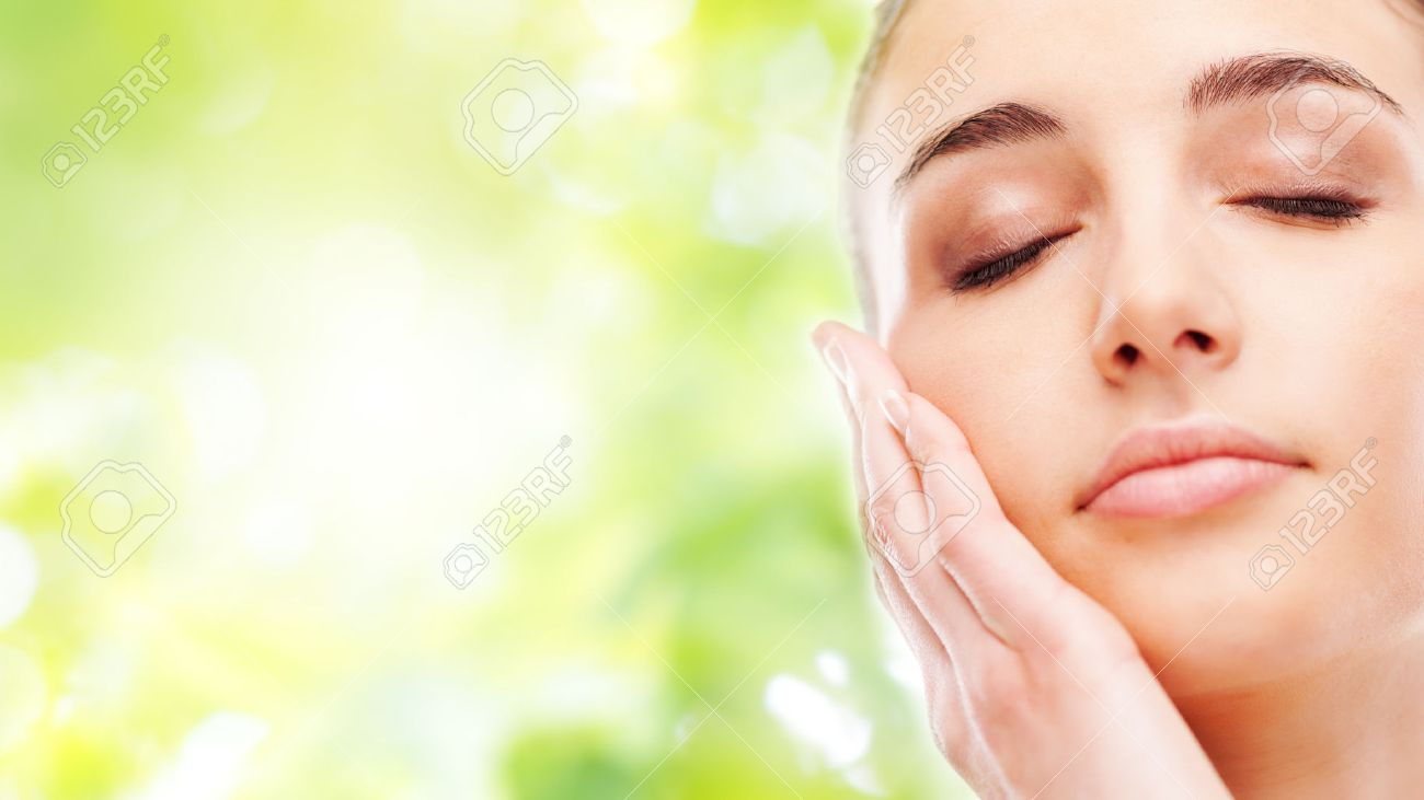 Beautiful young woman touching her radiant face skin with eyes closed on green background - 38570564