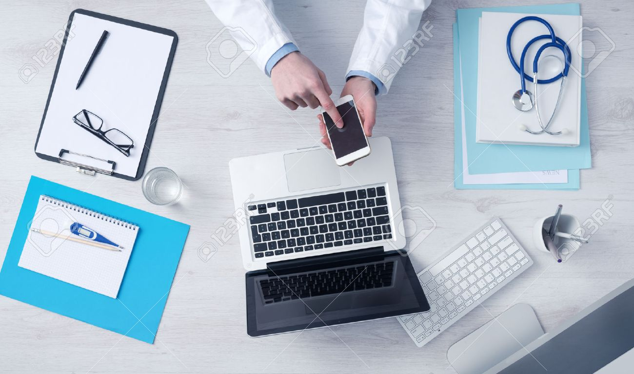 Doctor working at office desk and using a mobile touch screen phone computer and medical equipment all around top view Stock Photo - 39447102
