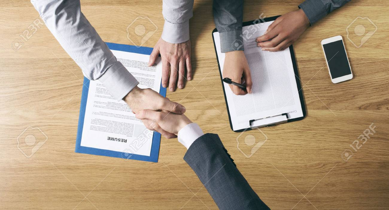 Employer hiring and giving an handshake to the candidate after the job interview hands close up top view Stock Photo - 39447108