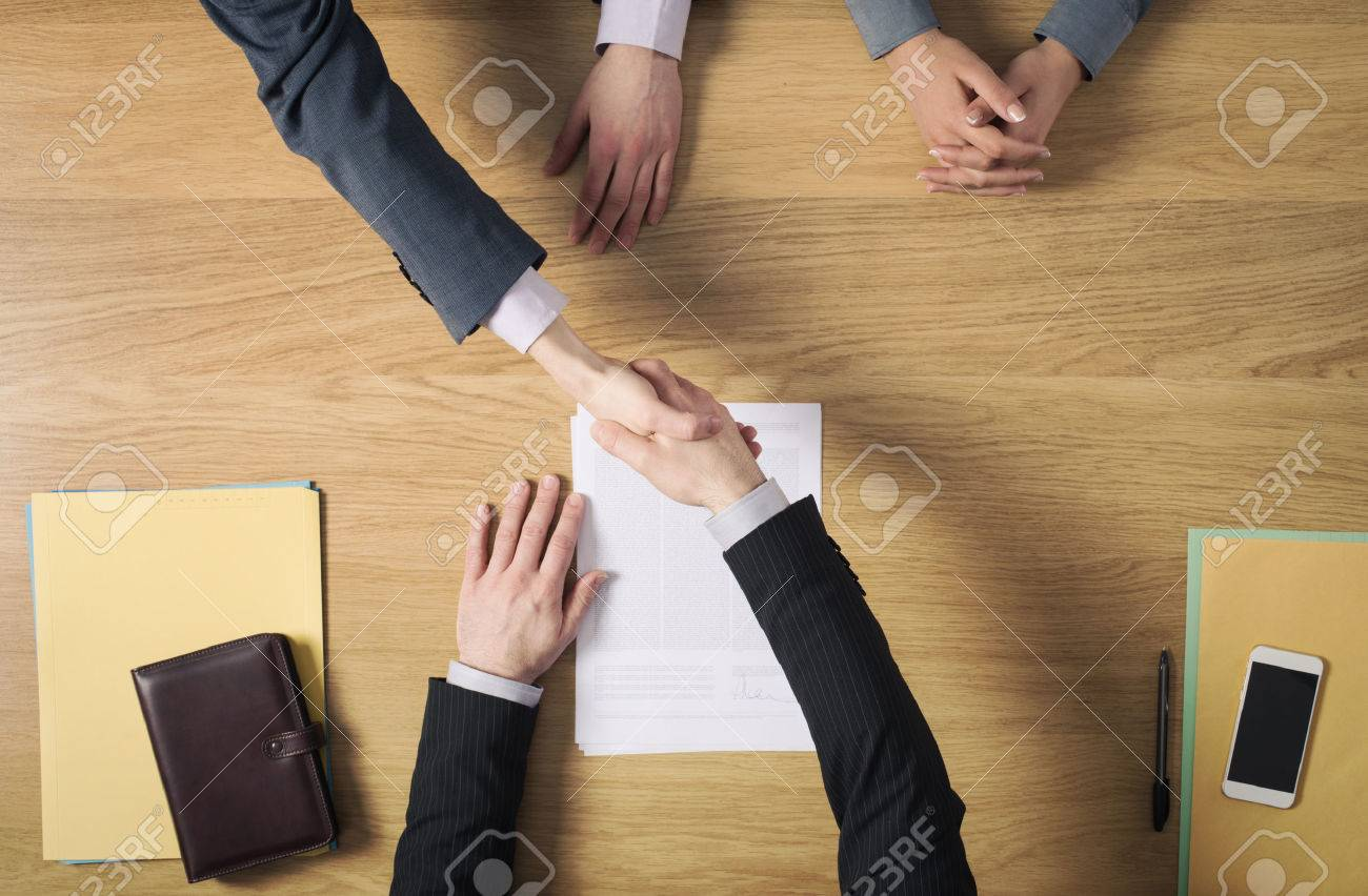 Business people at office desk handshaking after signing an agreement hands top view unrecognizable people Stock Photo - 39447112