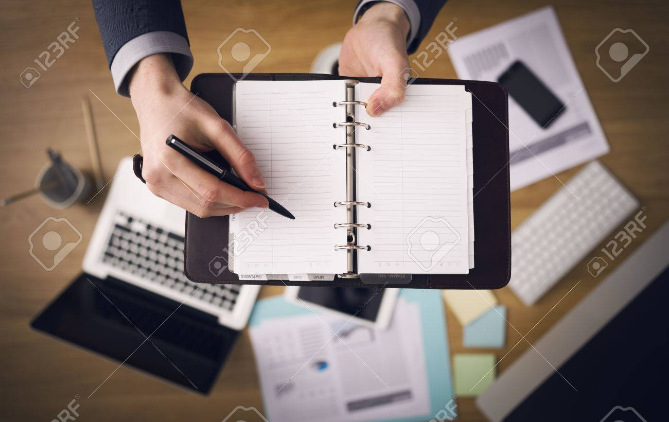 Businessman working at office desk and writing down notes on his agenda laptop and financial report on background top view. Stock Photo - 39447113