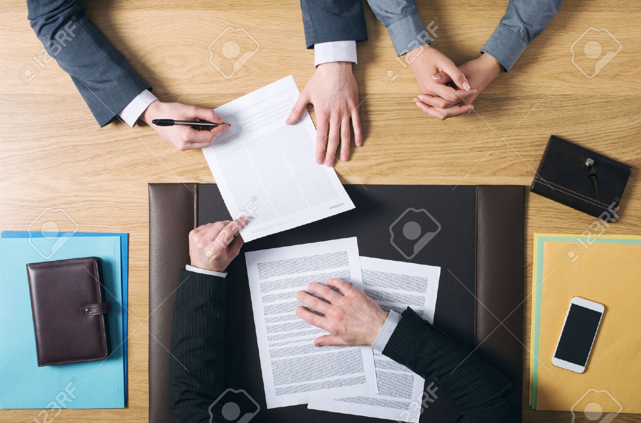 Business man and woman sitting at the lawyers's desk and signing important documents hands top view unrecognizable people Stock Photo - 39447143