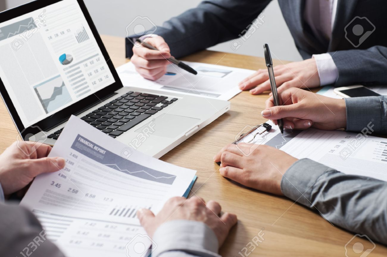 Business professionals working together at office desk, hands close up pointing out financial data on a report, teamwork concept Stock Photo - 41135189