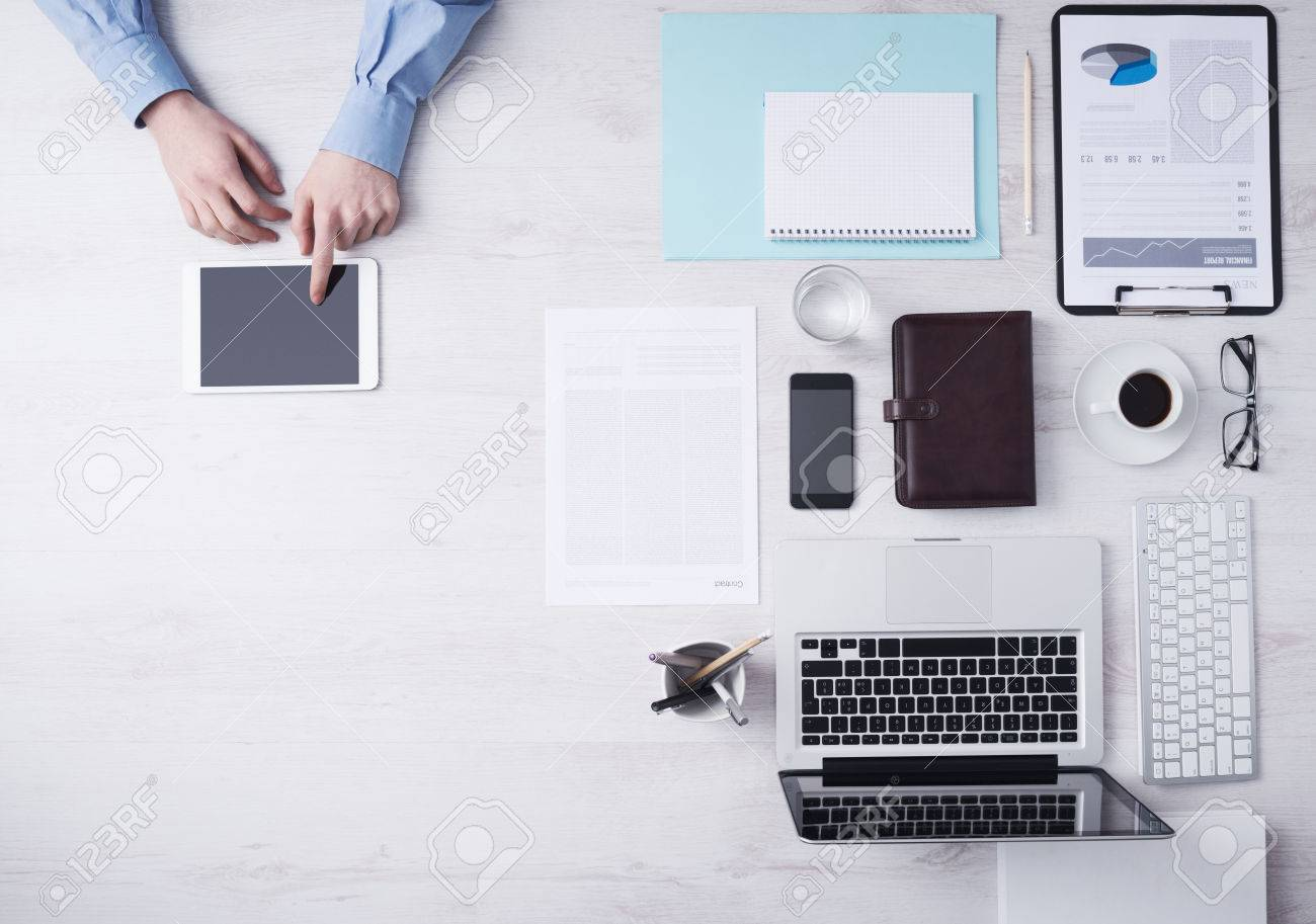 Businessman working at office desk and using a digital touch screen tablet hands detail, computer and objects on the right, top view Stock Photo - 41135724