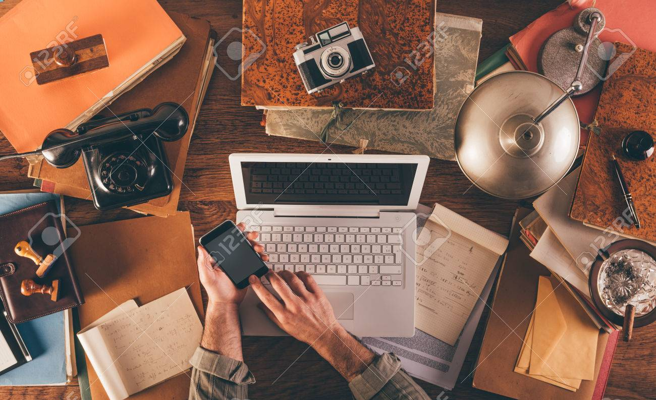 Messy vintage desktop with laptop and male hands using a smart phone, top view Stock Photo - 41135800