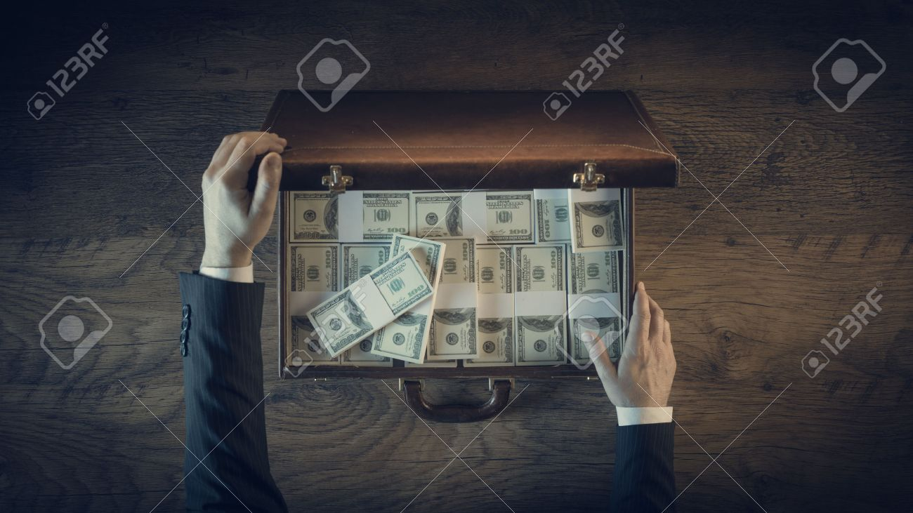 Rich businessman opening a leather briefcase filled with dollar packs, top view, unrecognizable person Stock Photo - 41135807