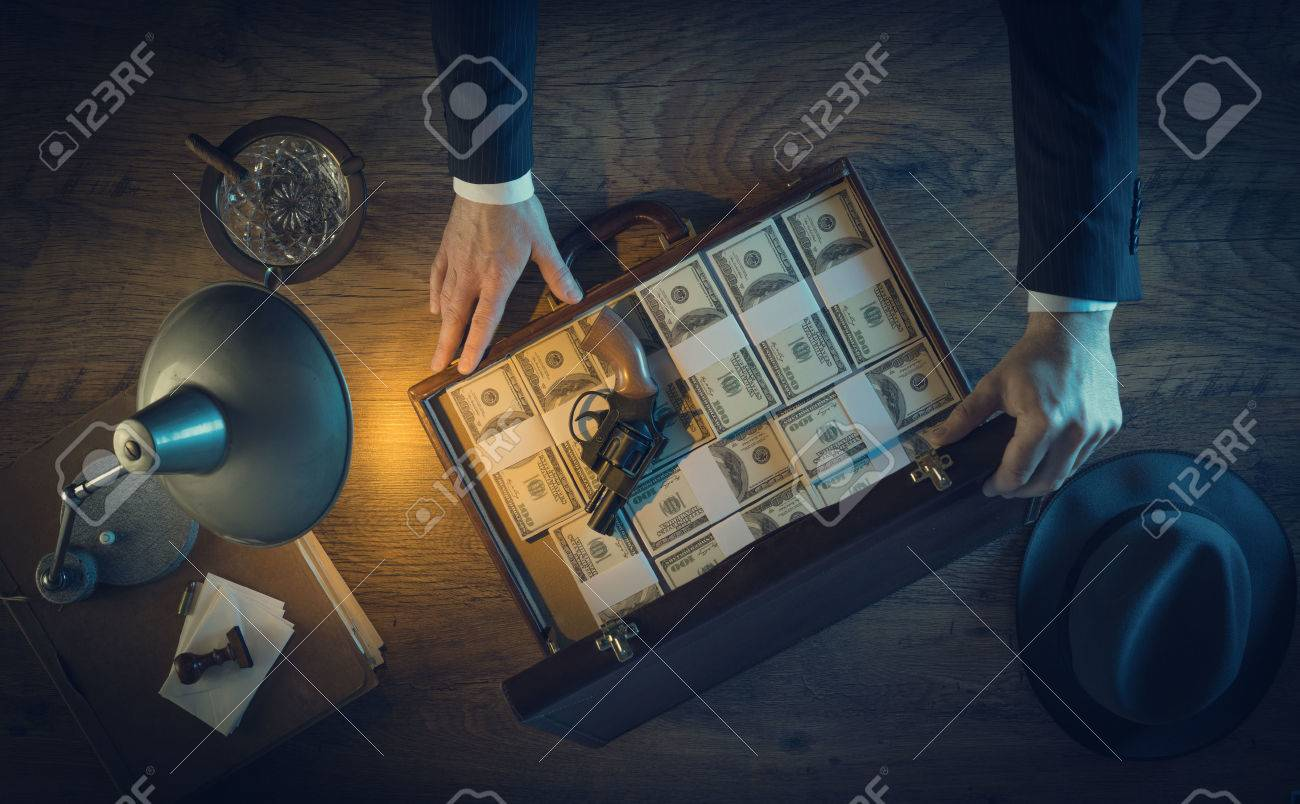Vintage gangster with a gun and a leather briefcase filled with dollar packs, top view, 1950s film noir style Stock Photo - 41135965