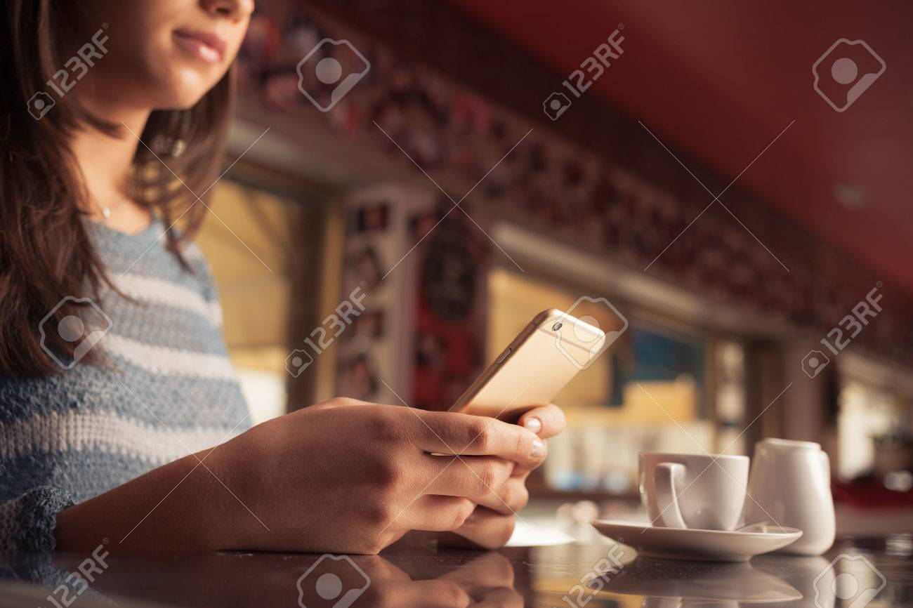 Woman leaning on the bar counter and text messaging with her mobile, hands close up Stock Photo - 43016318
