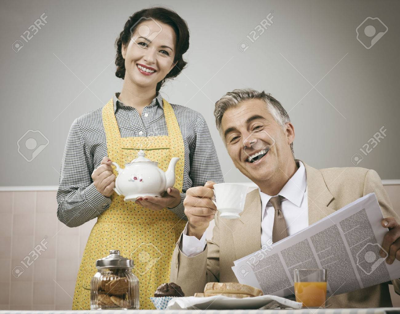 1950s beautiful woman serving tea for breakfast to her smiling husband Stock Photo - 44583413