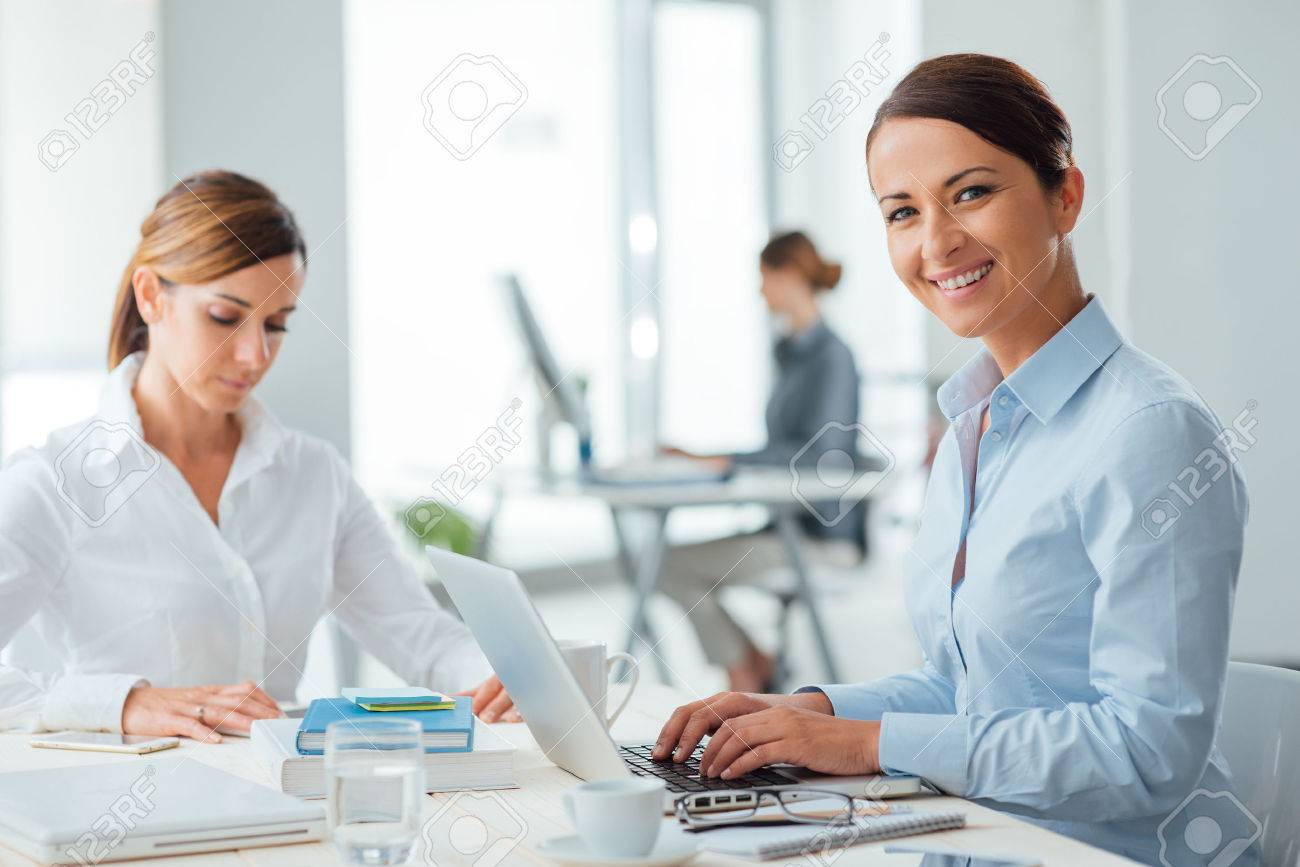 Successful confident business women and entrepreneurs working at office desk, one is smiling at camera, office interior on background Stock Photo - 44655760