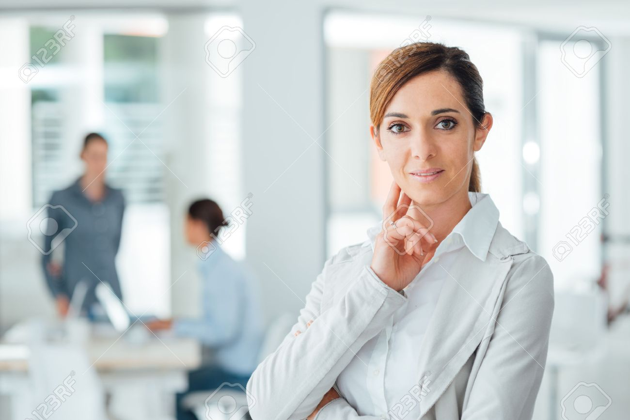 Confident woman entrepreneur posing in her office and smiling at camera, success and women empowerment concept Stock Photo - 44655764