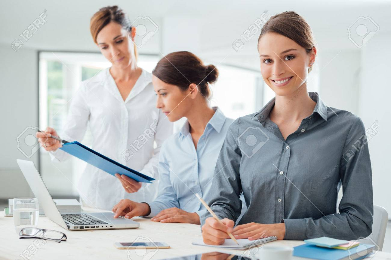 Business women team working at office desk and pointing on a report, one is smiling at camera Stock Photo - 44655770