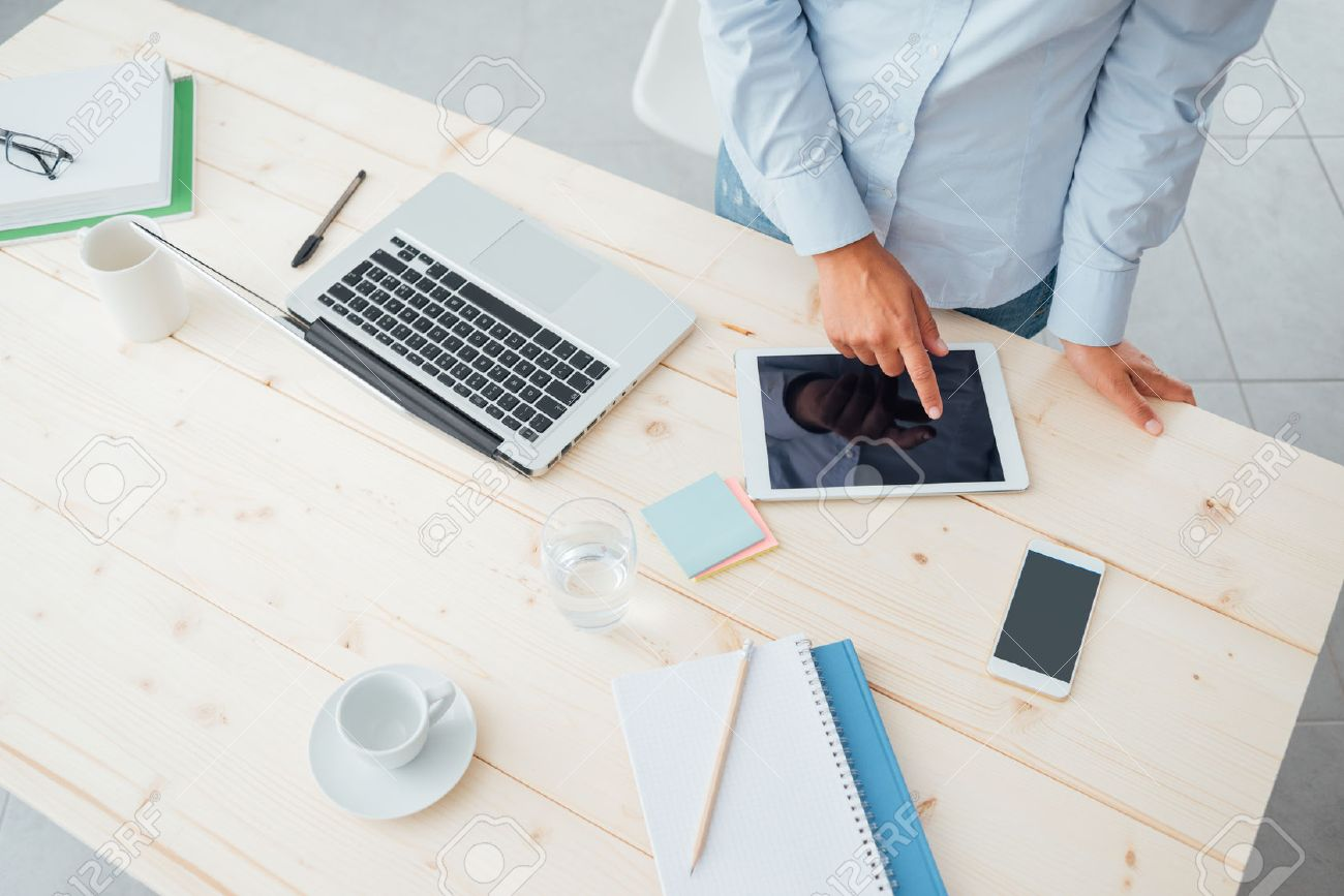 Unrecognizable business woman working at office desk and using a touch screen tablet on a wooden surface Stock Photo - 44866720