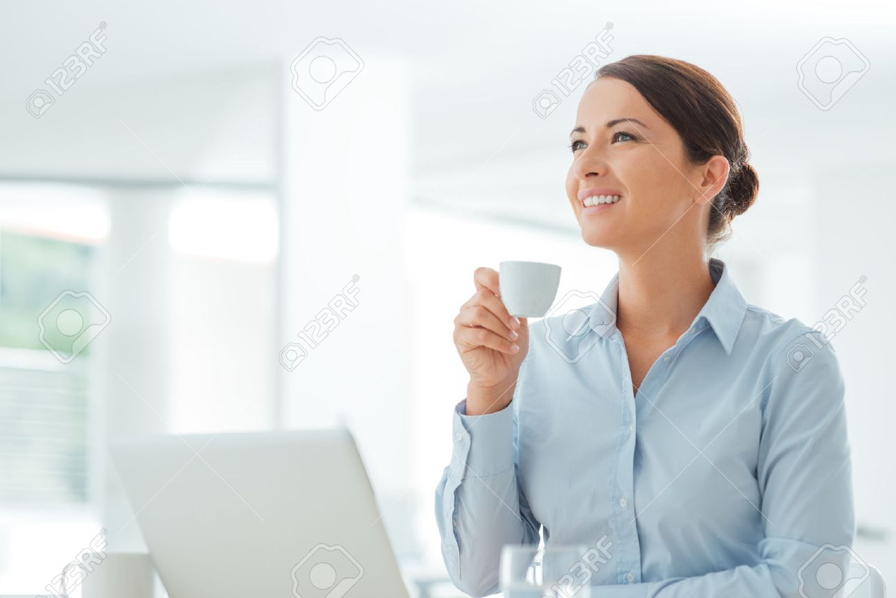Attractive smiling business woman sitting at office desk, holding a cup of coffee, she is relaxing and looking away Stock Photo - 44655549