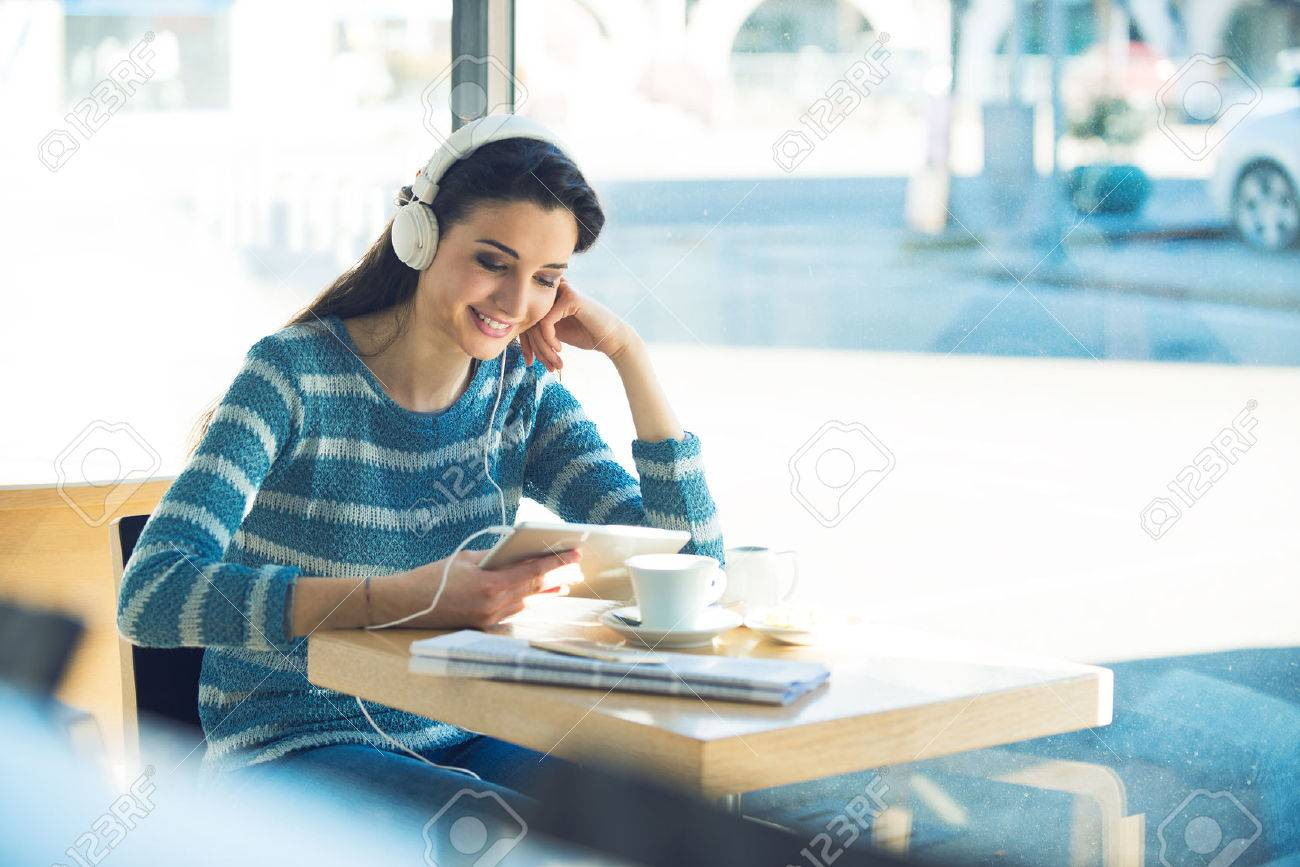 Smiling young woman at the cafe with headphones listening to music and using a tablet Stock Photo - 44655630