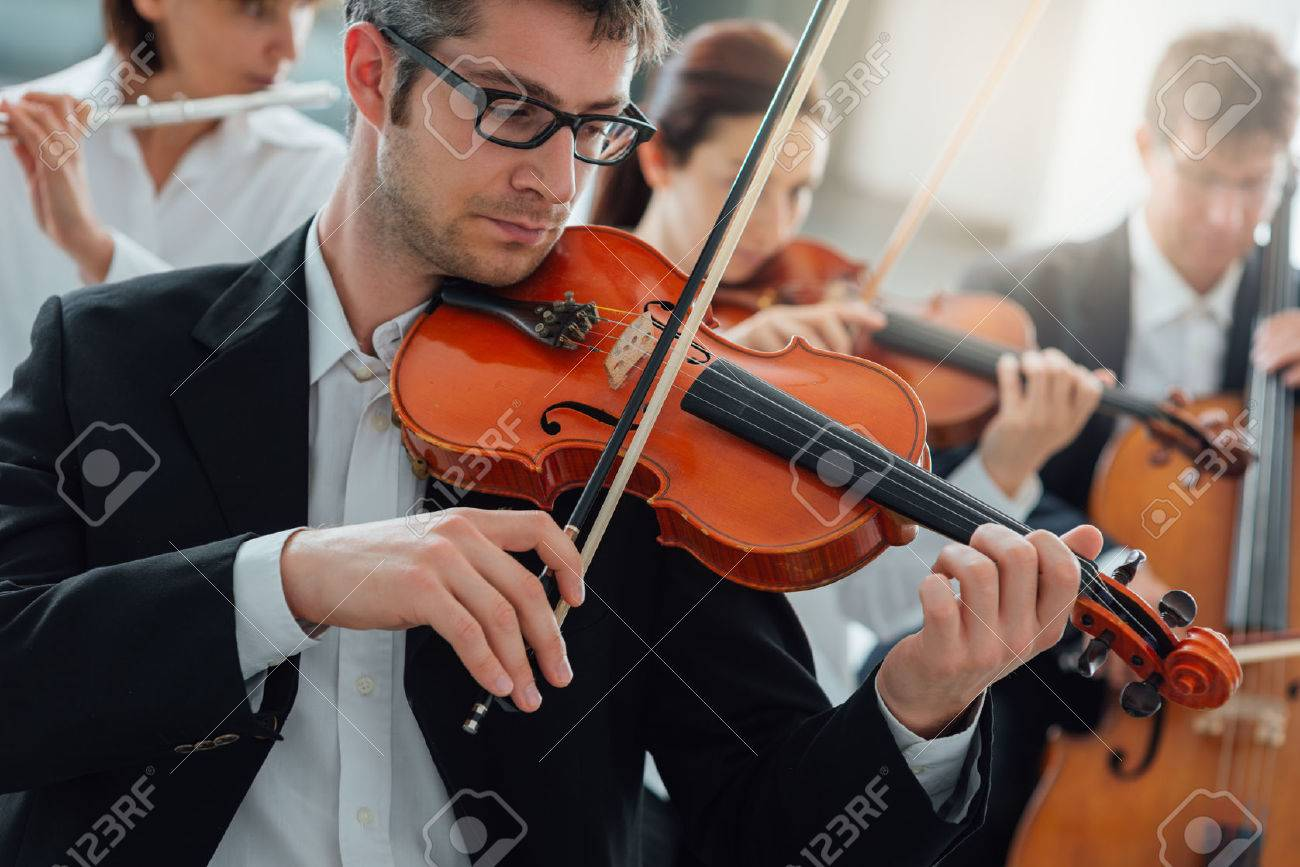 Classical music symphony orchestra string section performing, male violinist playing on foreground, music and teamwork concept Stock Photo - 46506705