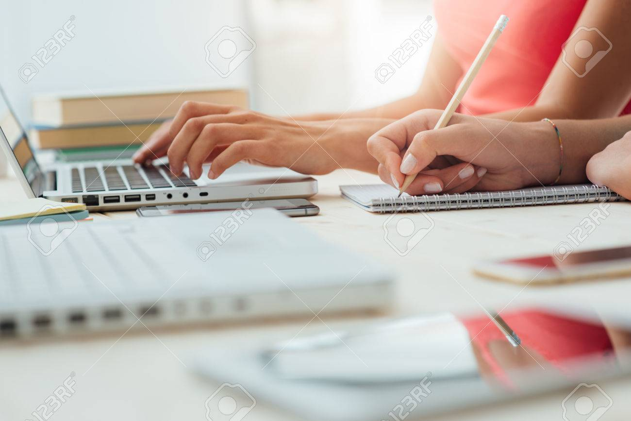 Teen girls studying at desk and doing homeworks, one is using a laptop and the other one is writing on a notebook, education concept, unrecognizable people Stock Photo - 47105493