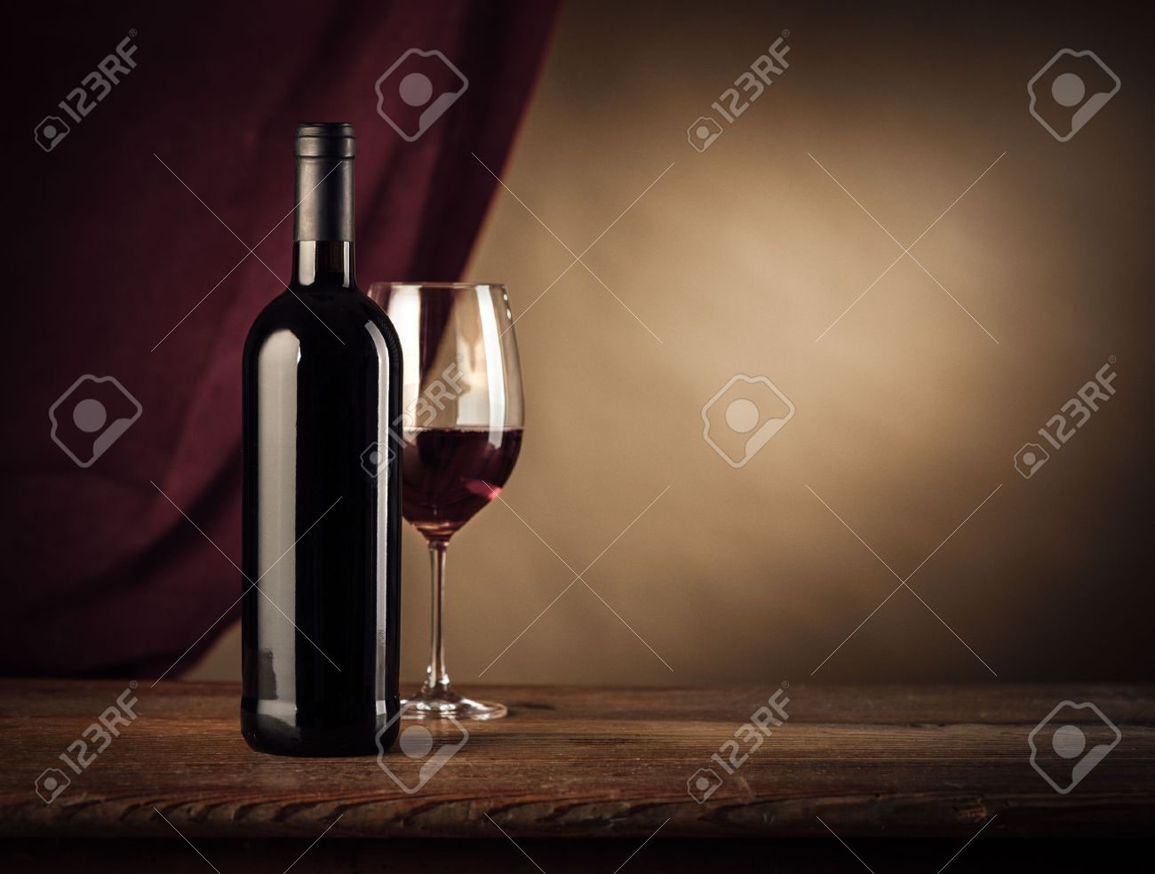 Red wine bottle and glass on a rustic wooden table, red cloth on background Stock Photo - 47105491
