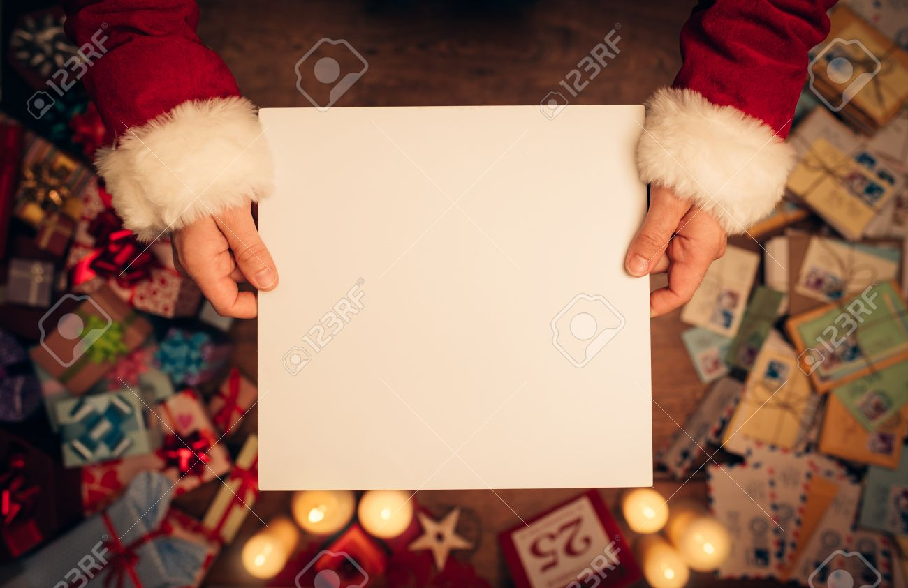 Santa Claus holding a blank sign, hands close up, top view, desktop with Christmas gifts and letters on background Stock Photo - 48492500