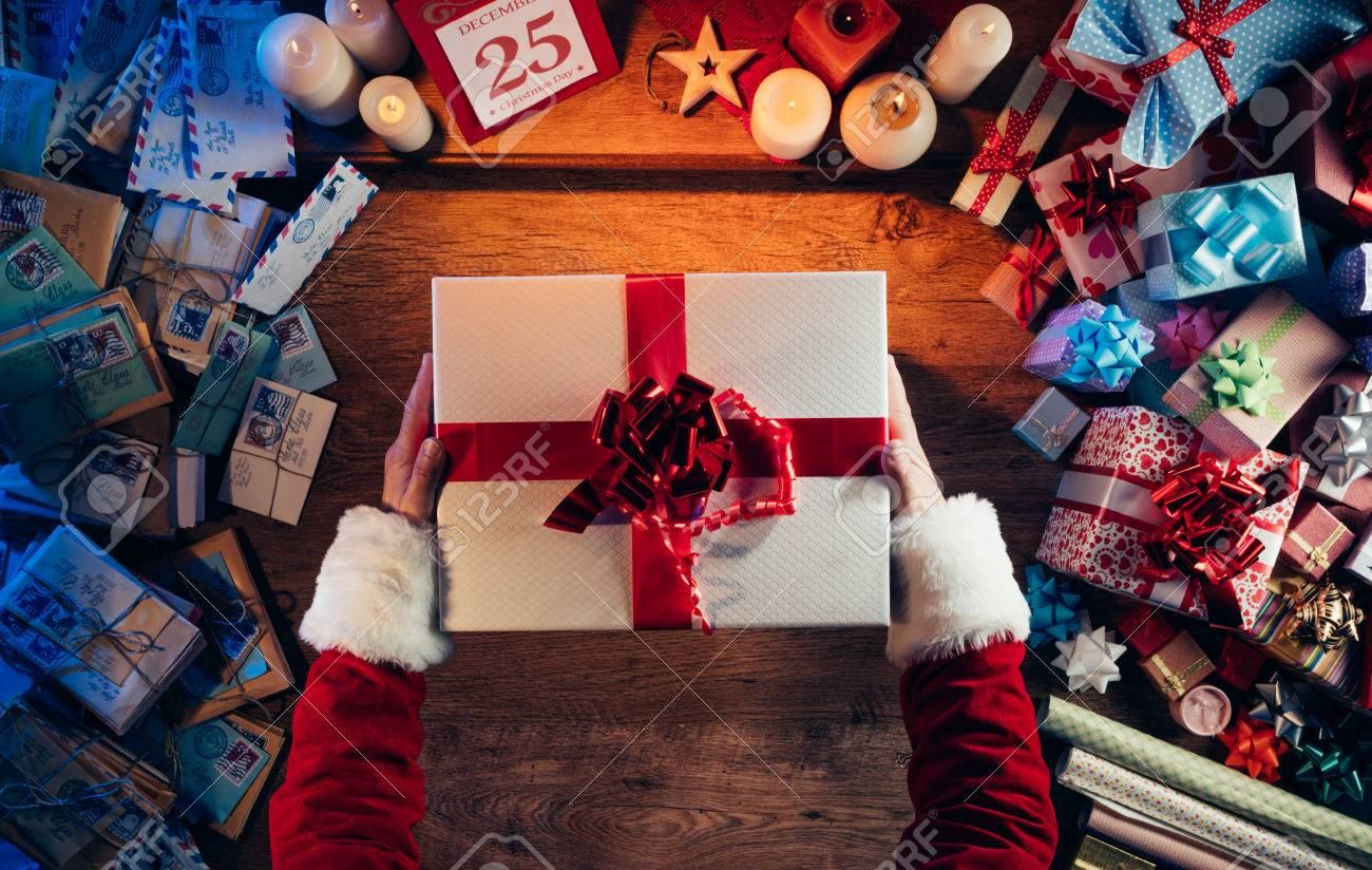 Santa Claus holding a beautiful Christmas gift box, letters and presents all around, hands top view Stock Photo - 48541937