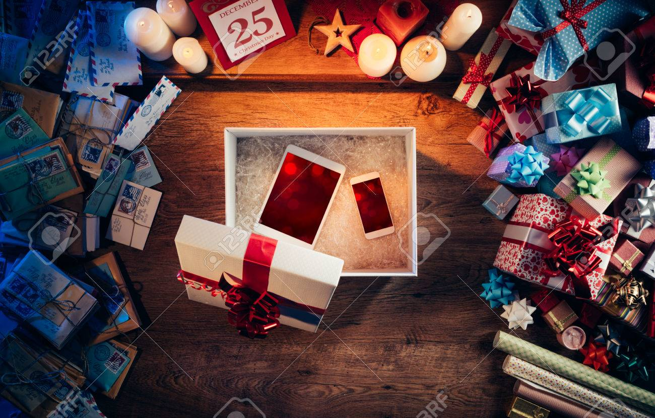 Open Christmas gift box with a tablet and a smart phone inside, presents and letters all around, top view Stock Photo - 48720547