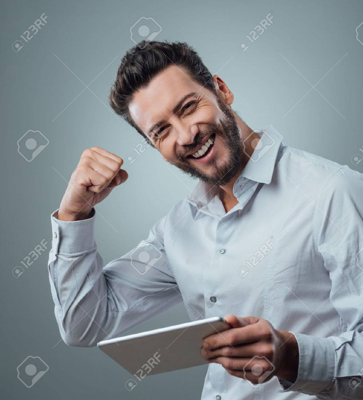 Cheerful smiling man receiving good news on tablet with fist raised Stock Photo - 48738853