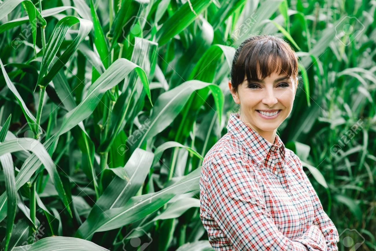 Agricultrice Enthousiaste et entrepreneur posant dans la récolte de maïs et souriant à la caméra, de l'agriculture et le concept de la culture Banque d'images - 48739564