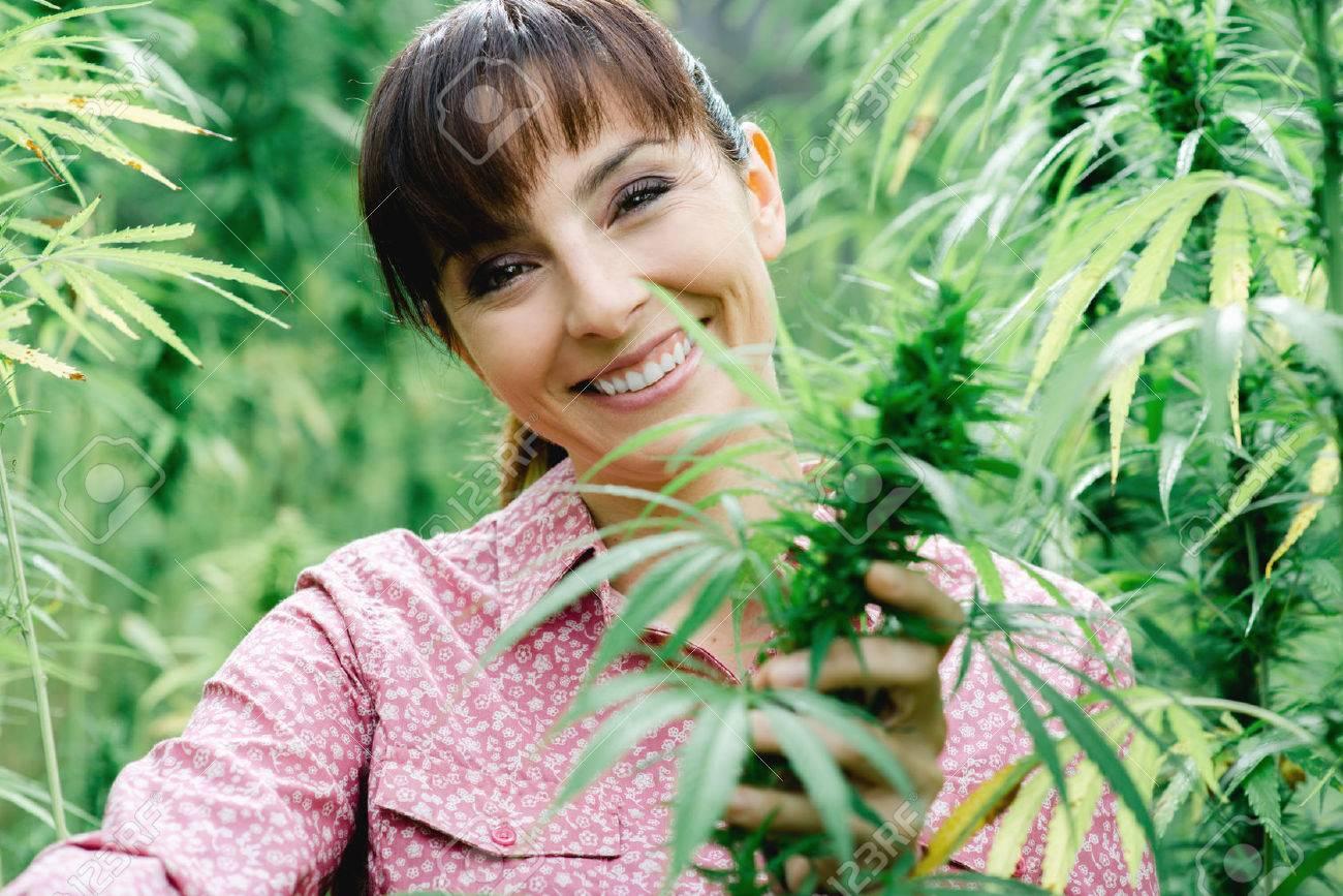 Jeune femme souriante dans un champ de chanvre vérifier plantes et de fleurs, l'agriculture et le concept de la nature Banque d'images - 48740230