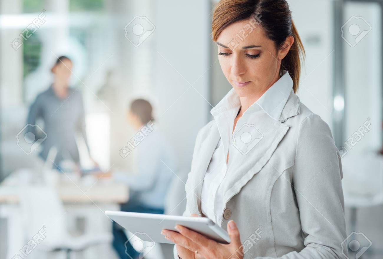 Confident professional business woman standing in the office and using a digital touch screen tablet Stock Photo - 48740277
