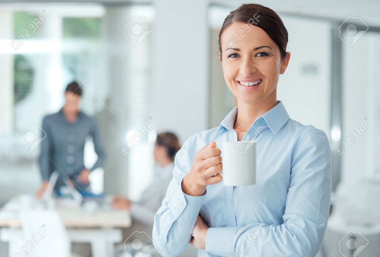 Happy confident business woman having a coffee break and holding a mug, office workers on background Stock Photo - 48740823