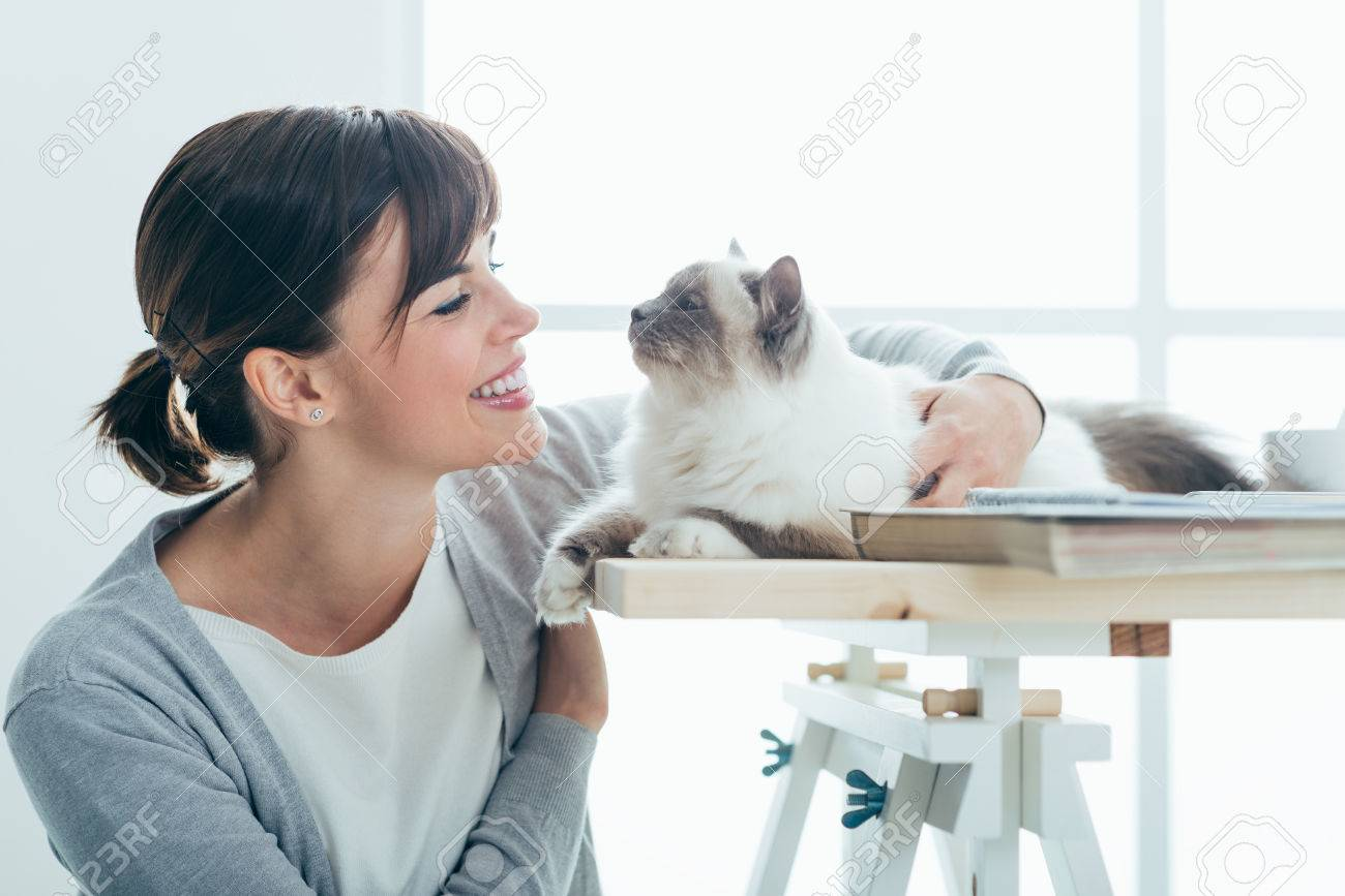 Happy smiling woman at home cuddling and holding her lovely cat on a table, pets and togetherness concept Stock Photo - 52944552