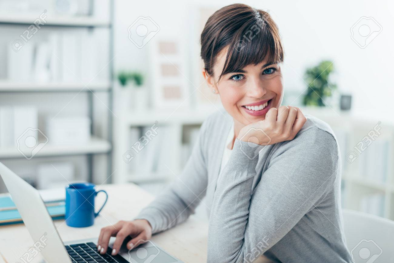 Happy confident businesswoman sitting at office desk and working with a laptop, she is smiling at camera Banque d'images - 52944765
