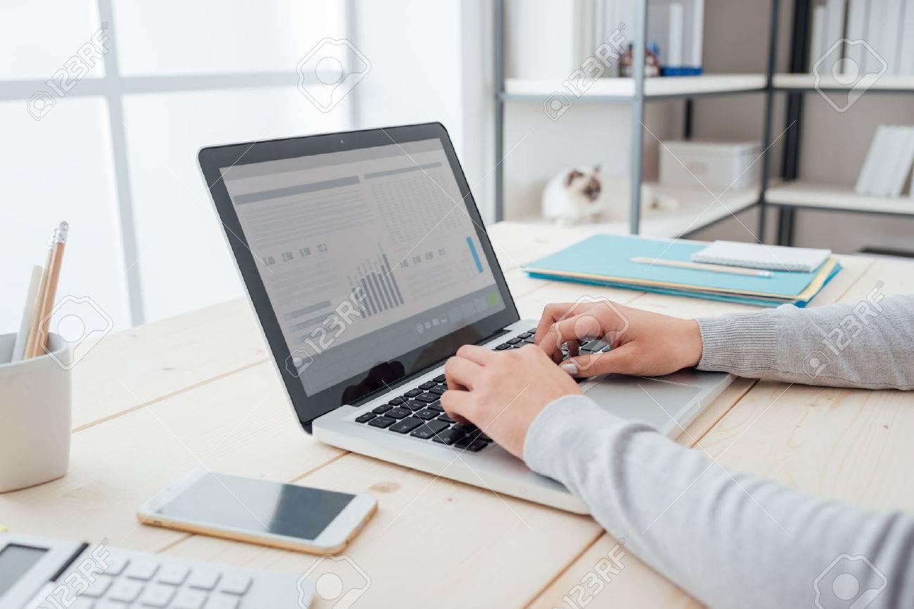 D'affaires assis à son bureau de bureau et en tapant sur un ordinateur portable mains close up Banque d'images - 52944788